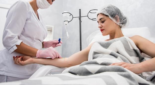 Врач косметолог производит косметологическую процедуру с капельницей. infusion. молодая женщина в салоне красоты.