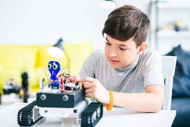 엔지니어링 프로젝트를 준비하는 동안 자신의 로봇 장치를 구성하는 독창적인 집중 남학생