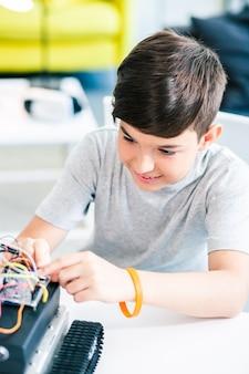 탁자에 앉아 로봇 장치를 만드는 독창적인 기뻐하는 남학생