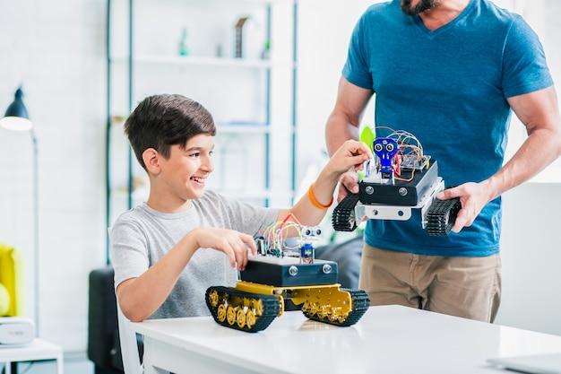 彼の父が彼を助けている間、エンジニアリングプロジェクトに取り組んでいる独創的な笑顔の男子生徒