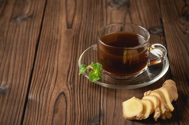ホットジンジャージュースと生ingerは木製のテーブルでスライスされました。