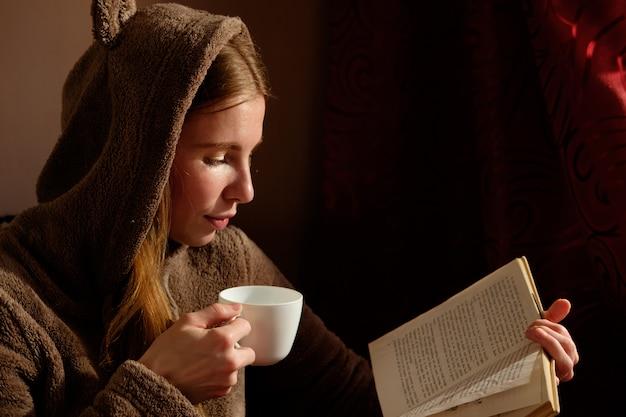 面白いフーディ読書、コーヒーを飲み、ソファーに横になっていると笑みを浮かべて赤毛生inger少女