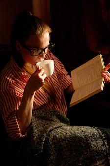 本を読んで、コーヒーを飲みながら、ソファーに横になっていると笑みを浮かべてストリップシャツの赤毛生inger少女