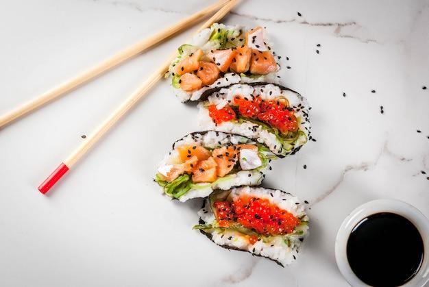 トレンドハイブリッド食品。日本アジア料理。ミニ寿司タコス、サーモンのサンドイッチ、林わかめ、大根、生inger、赤キャビア。白い大理石のテーブル、箸、醤油。コピースペーストップビュー