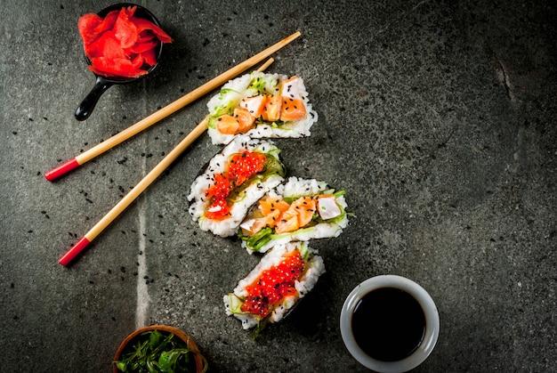トレンドハイブリッド食品。日本アジア料理。ミニ寿司タコス、サーモンのサンドイッチ、林わかめ、大根、生inger、赤キャビア。黒い石のテーブル、箸、醤油。コピースペーストップビュー