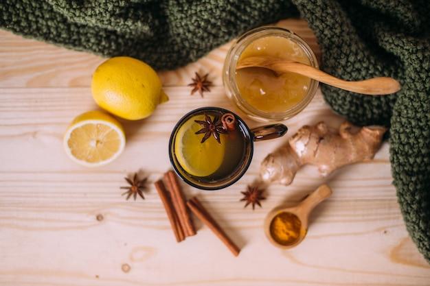 レモン、蜂蜜、生inger、シナモン、アニスを入れた温水カップ。