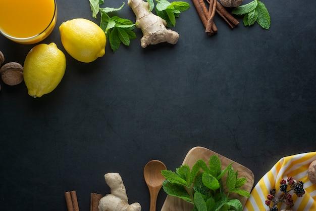 暗い表面に生inger、レモン、ミントの葉、