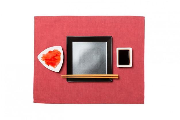 赤いナプキンに寿司、生inger、醤油の箸で空の黒い正方形プレート