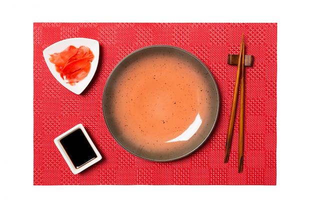 寿司と醤油の箸、赤いマット寿司に生ingerの空の丸い茶色のプレート