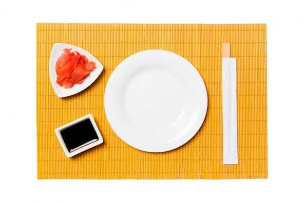 寿司と醤油、黄色の竹マットの背景に生ingerの箸で空の丸い白いプレート