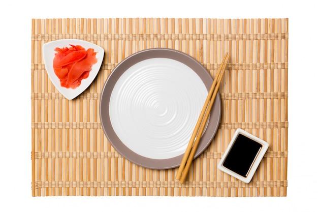 寿司と醤油、黄色の竹マットの背景に生ingerの箸で空の白い丸皿。設計用のコピースペースを含む平面図