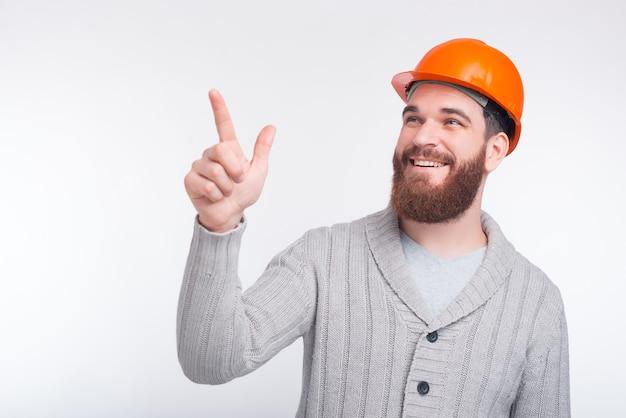 Ingineer, architect 또는 constructor 남자는 흰색 배경에 뭔가 가르키고 있습니다.