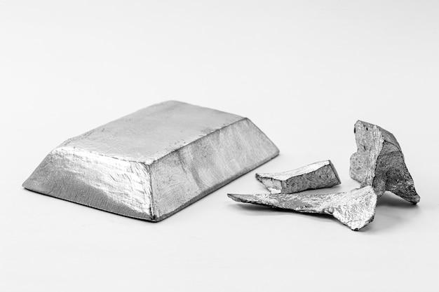Слиток и металлический стержень рядом с металлической рудой, материал, используемый в общей промышленности
