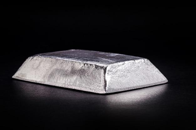 絶縁された黒い背景、合金の製造または鉄骨構造の亜鉛メッキに使用される金属で分離されたインゴットまたは亜鉛棒