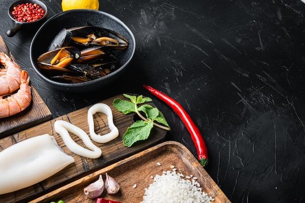 Ингредиент для испанской паэльи из морепродуктов с рисом, горохом, перцем и моллюсками на черном текстурированном фоне с местом для текста