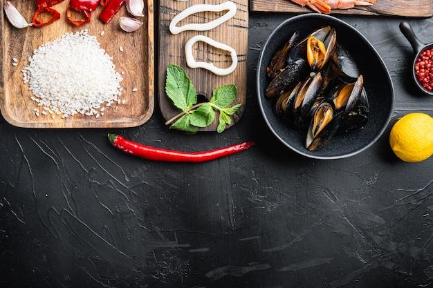 Ингредиент для испанской паэльи из морепродуктов с рисом, горохом, перцем и моллюсками на черном текстурированном фоне