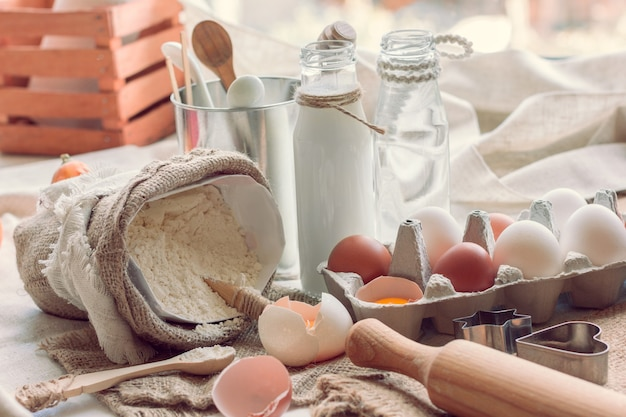 테이블에 계란, 밀가루, 우유 및 물로 베이킹 재료