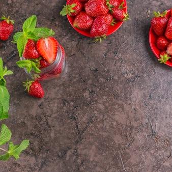 熟した甘いベリーとミントの葉が入ったガラス瓶に入った自家製ストロベリージャムまたはマーマレードの材料