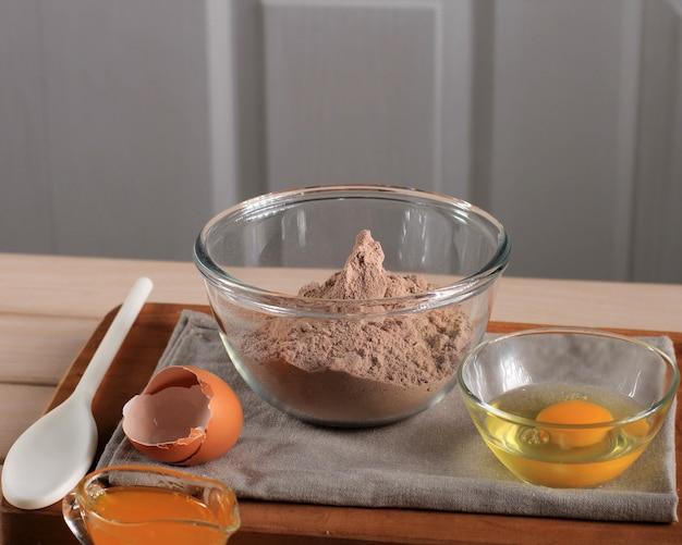 田舎または素朴なキッチンのチョコレートケーキ(ブラウニー)の材料。ヴィンテージウッドテーブルの生地レシピ成分(卵、小麦粉、ミルク、バター、砂糖)