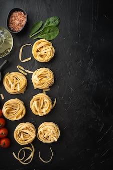 Ingredient of traditional mediterranean cuisine uncooked pasta tagliatelle set, on black stone