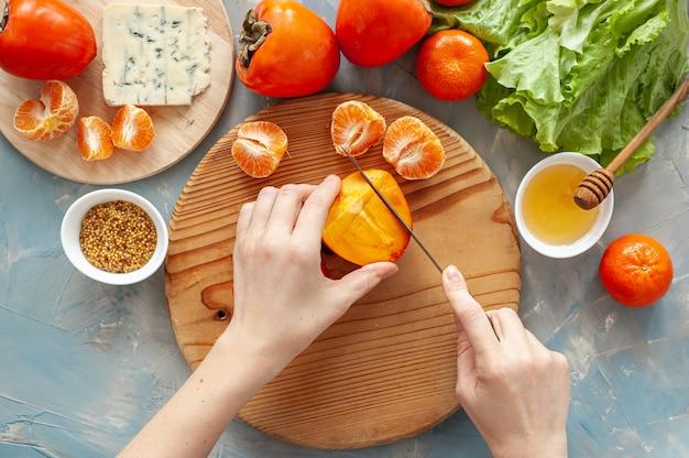 Ингредиенты и процесс приготовления витаминного зимнего салата с хурмой, мандаринами и голубым сыром. шаг за шагом. женщина режет хурму на круглой деревянной доске. вид сверху.