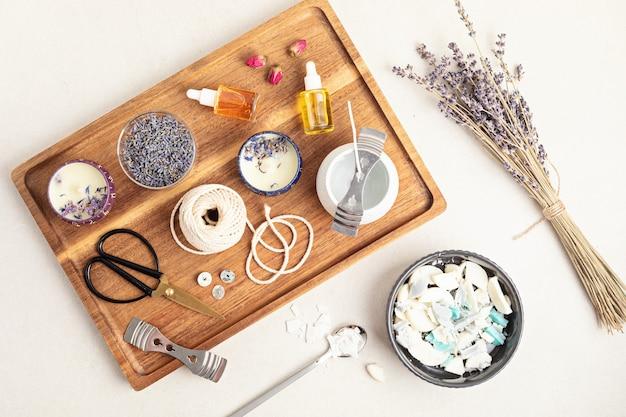 오래된 양초 잔여물로 만든 수제 아로마 양초 재료와 도구. 왁스, 에센셜 오일, 심지, 냄비. 공예 취미, 중소기업, 장인 제품 개념