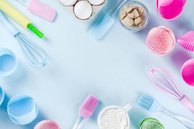 Ингредиенты и посуда для выпечки - яйца, мука, сахар, масло сливочное, молоко на голубом фоне