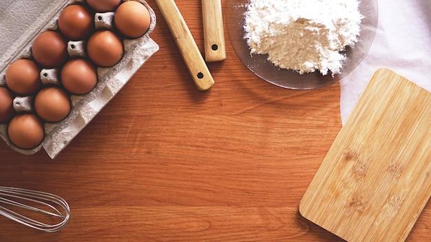 パステルカラーの木製の背景、上面図で焼くための材料と道具。キッチン、料理、イースターのコンセプト