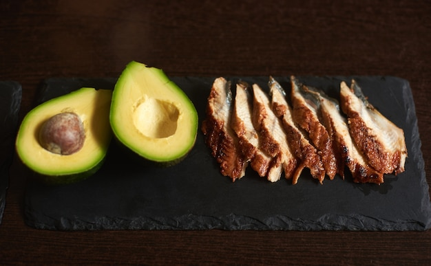 Ingredients avocado and eel on the black stone plate