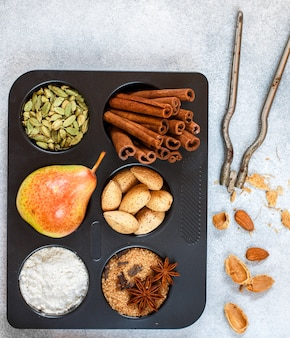 Ingredients for baking-flour, fruit pear, brown sugar, star anise, cinnamon, cardamom, cloves, almonds