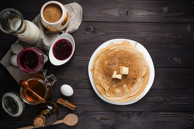 Ingredients for baking pancakes on a wooden table, top view