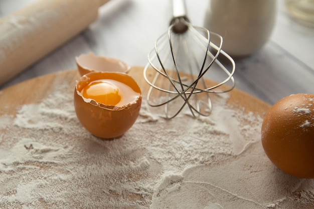 The ingredients for baking on the table are wheat flour on a board eggs milk and a whisk