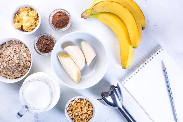 Ingredients for banana smoothie on a white. healthy eating concept.