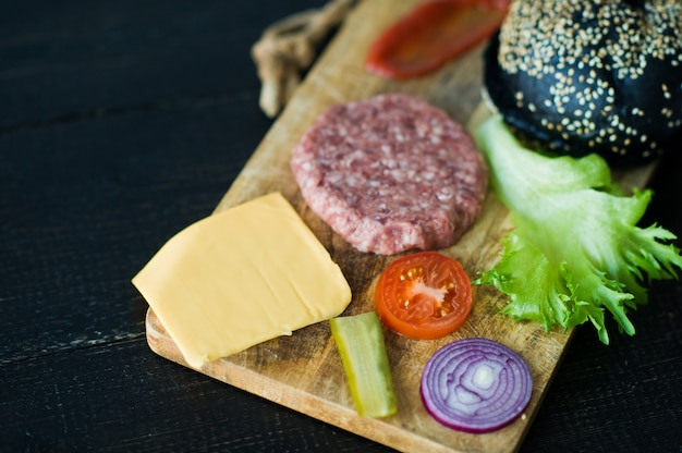 Ingredients for black burger on wooden chopping board, black background.