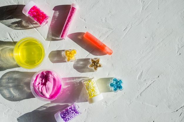 Ингредиенты, бутылки, баночки для изготовления, украшения популярной детской игрушки из клея. самодельный модный слайм розового, желтого цвета с шариками для развлечений и хобби в круглых коробках.