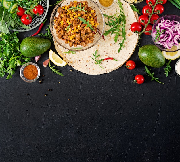 Ingredients for burritos wraps with beef and vegetables on black. mexican food. top view. flat lay