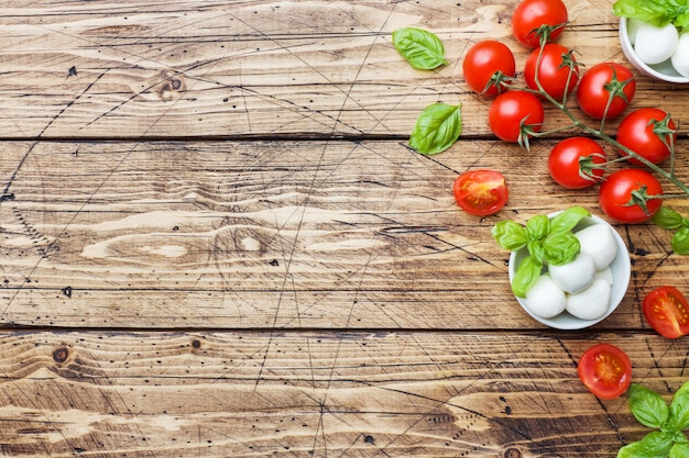 The ingredients for a caprese salad. basil, mozzarella balls and tomatoes with copy space.