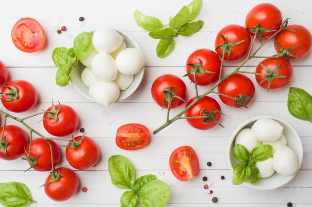 The ingredients for a caprese salad. basil, mozzarella balls and tomatoes