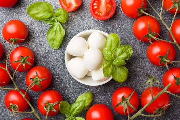 The ingredients for a caprese salad. basil, mozzarella balls and tomatoes.