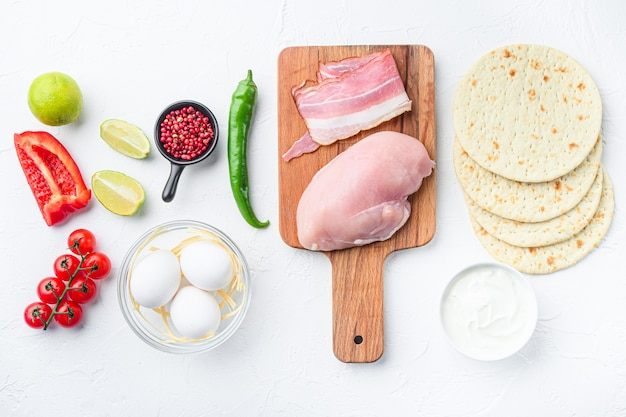 Ingredients for chicken tacos, tomatoes, corn, egg, pepper, lime chicken meat and tortillas over white