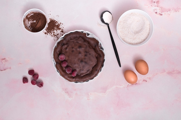 Ingredients for chocolate cake with raspberry toppings on pink backdrop