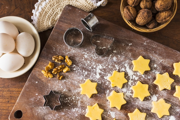 Ingredients and cookie cutters near raw biscuits