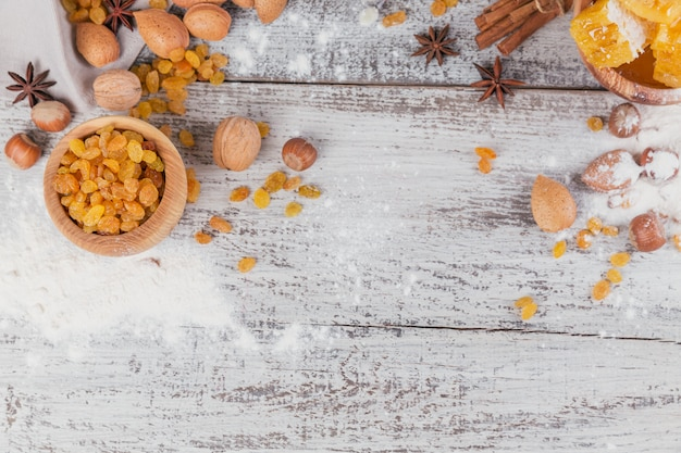 Ingredients for cooking bread or cookies with honeycomb, flour, raisines, mix of nuts, spices