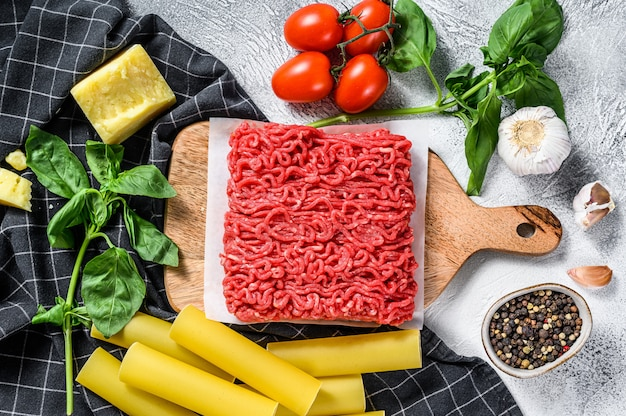 Ingredients for cooking cannelloni pasta with ground beef. italian cuisine. gray background. top view
