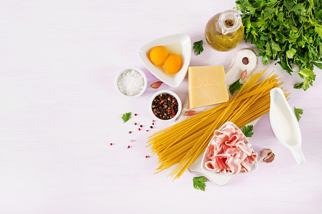 Ingredients for cooking carbonara pasta, spaghetti with pancetta, egg, peppers, salt and hard parmesan cheese.