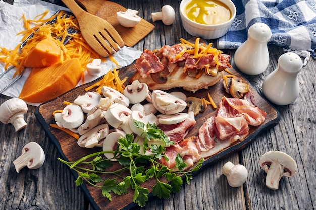 Ingredients for cooking chicken breasts with sauteed mushrooms, crispy bacon,  melted cheese and honey mustard dipping sauce