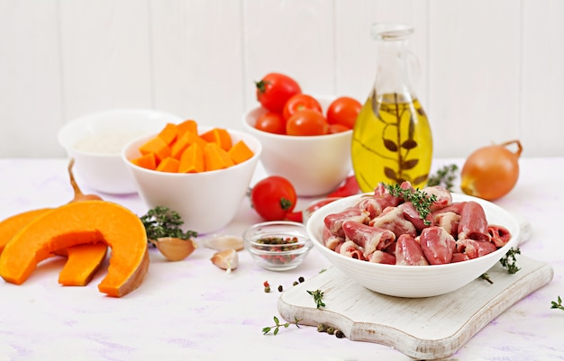 Ingredients for cooking chicken hearts with pumpkin and tomatoes in tomato sauce. the garnish is served with boiled rice.