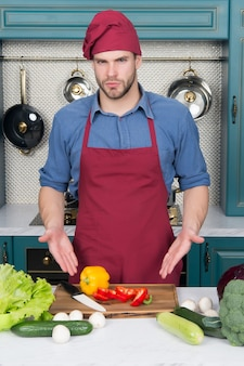 Ingredients for cooking dishes. man point at vegetables on table. cook in chef hat and apron in kitchen. vegetarian menu and healthy diet. food preparation and cooking recipes.