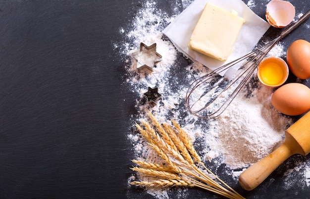 Ingredients for cooking: flour, butter, eggs on dark