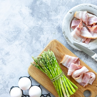 Ingredients for cooking on a gray concrete background. a bunch of fresh green asparagus, eggs and bacon. top view. copy space